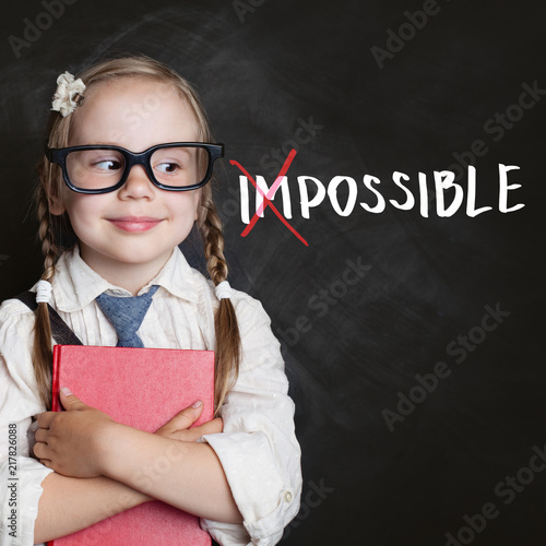 Foto Murales Smart kid with red book and putting a cross over impossible on blackboard background