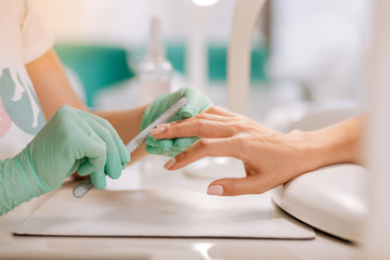 Polishing nails. Professional nail master wearing bright gloves using file while polishing nails of her client