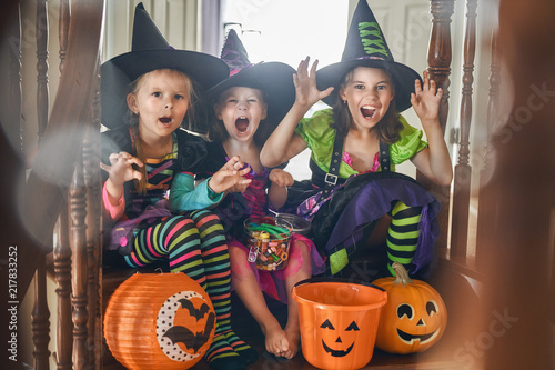 Leinwanddruck Bild Laughing children in witches costumes.