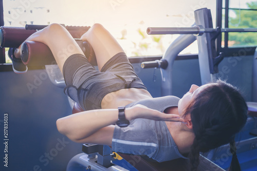 Plexiglas Fitness Young woman doing sit ups exercise with machine at fitness gym..
