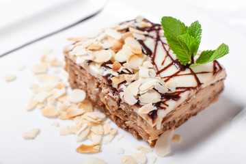 Almond cake. Piece of Cake with leaf mint on a Plate. Sweet food. Sweet dessert. Food background. Close up.