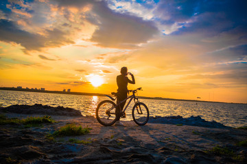 Silhouette of a young woman with a bicycle on the lake at sunset