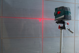 Installation of new tiles on the wall using a laser level - 217842482