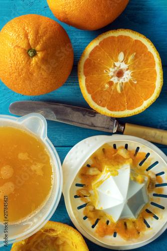 Aluminium Sap Making orange juice , oranges with manual citrus juicer on rustic table , vertical , top view