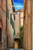 Narrow old street in Siena, Tuscany, Italy. Stone lane and typical medieval architecture