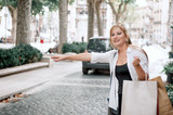 Young happy hipster girl with shopping bags catch a taxi on the street. - 217850803