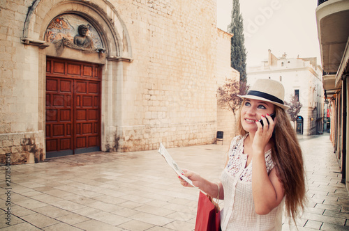 Foto Murales Girl is walking on the tourist city of Spain, Figueres.  Women with mobile phone and city map on the street. Euro-trip.
