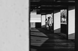 Black and white shot of Couple holding hands and standing near parking wall