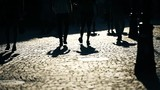 Pedestrians silhouettes at sunset on a cobblestone street - 217856844