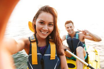 Loving couple kayaking on lake sea in boat make selfie by camera.