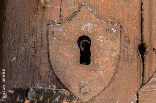 Leinwanddruck Bild A keyhole with a shield in the old door.