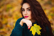 Beautiful young woman. Dramatic outdoor autumn portrait of sensual brunette female with long hair. Sad and serious girl.