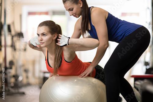 Leinwanddruck Bild Fitness trainer helping young girl doing back exercises in gym