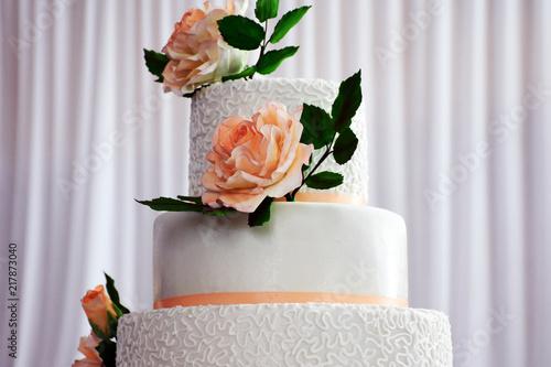 Foto Murales Big white wedding cake with peach flowers
