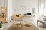 Wooden table and pouf on carpet in white living room interior with poster and workspace. Real photo