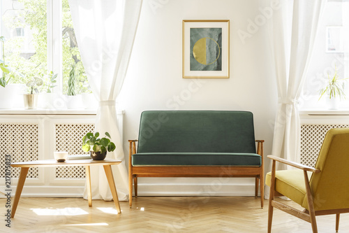 Leinwanddruck Bild Real photo of a mid-century living room interior with a sofa, coffee table, windows and painting