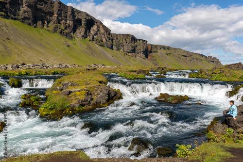 Urlaub in Island, Frau sitzt an Flusslandschaft mit kleinen Wassertreppen - 217894052