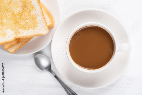 Wall mural Cup of coffee and sliced bread with honey topping on white table, top view
