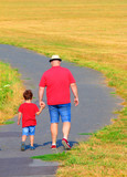 Overweight father with son walking on footpath. Hiking is outdoor sport for all. Summer vacations on countryside. - 217904210