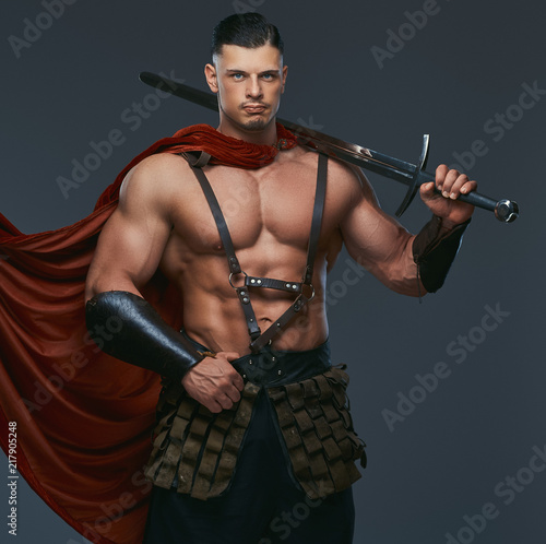 Portrait of ancient Greece warrior with a muscular body dressed in battle uniforms holds sword on his shoulder.
