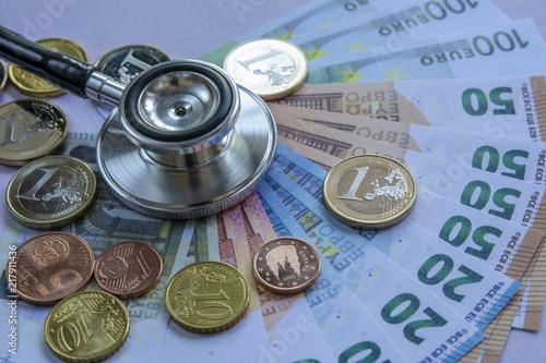 Foto Murales Coste de la medicina: estetoscopio sobre una pila de euros