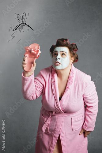 femme ronde avec peignoir et bigoudis chassant un moustique dessiné - 217916010