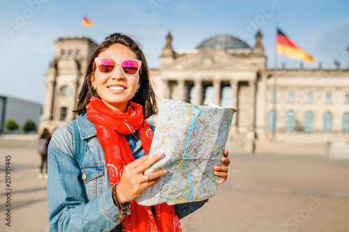 Beautiful young woman looking at map guide while standing in front of Bundestag building at sunset in Berlin. Travel in Germany concept © EdNurg