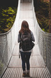 A young woman standing on a suspension bridge in an evergreen forest.