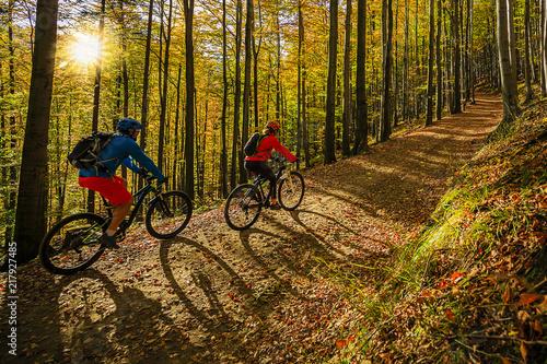 Jeździć na rowerze, halna rowerzysta para na cyklu śladzie w jesień lesie. Kolarstwo górskie w jesień krajobrazowym lesie. Mężczyzna i kobieta, jazda na rowerze MTB przepływu pod górę.