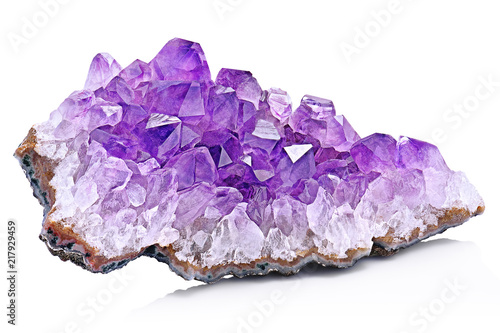 Violet Crystal Stone macro mineral. Purple rough Amethyst quartz crystals geode on white background, Uruguay - 217929459