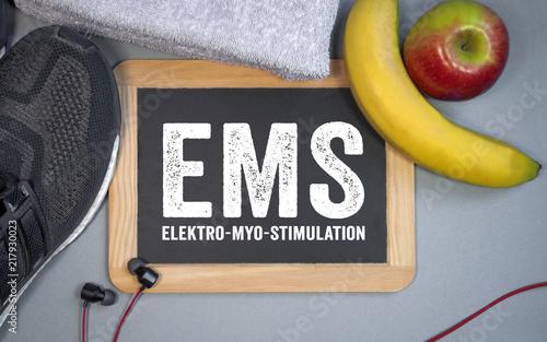 Foto Murales Tafel mit Sportschuhen Banane Apfel Handtuch Fitness EMS Elektro-Myo-Stimulation