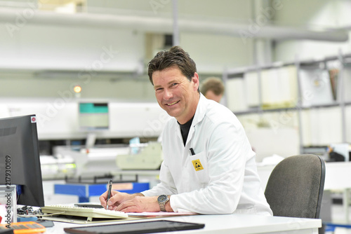 portrait of a friendly worker/ engineer in a modern factory at the desk - industrial fabric for  assembly of electronics products