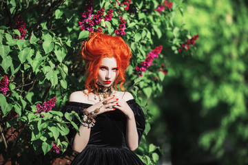Goth halloween attire. Gothic woman witch with pale skin and red hair in black gown and renaissance necklace on neck. Girl witch with red lips. Goth look. Renaissance attire for halloween. © iiievgeniy