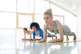 Diverse women standing in row on yoga mats and doing plank exercise training abs together in team - 217936468