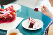 Leinwanddruck Bild - Crop unrecognizable woman eating Red Velvet cake with cup of tea in cafe