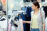 Beautiful young female in casual outfit looking at clothes on rail while standing in nice store - 217941814