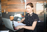 Stylish young woman using laptop and holding papers standing at counter in shop managing business