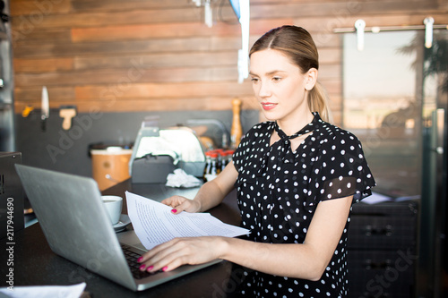 Stylish young woman using laptop and holding papers standing at counter in shop managing business  - 217944690