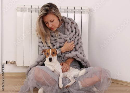 Foto Murales Cold home, freezing Woman Wrapped In Blanket Sitting Near Heater with her dog