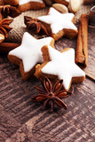 Christmas cookies and spices on brown wooden background.
