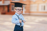 Little smart boy in spectacles, academic hat and glasses standing in the backyard of the school. Holds a magnifying glass in his hands - 217950693