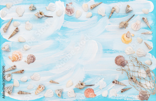 Sea shells fishing net blue wooden board Flat lay