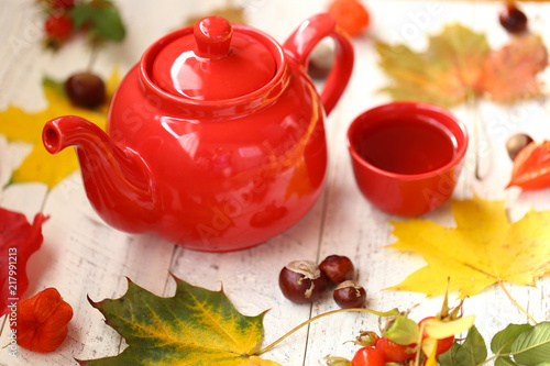 Autumn cozy tea drinking.red teapot, cup with tea, maple bright leaves, chestnuts, dogrose on shabby chic background.Autumn season.