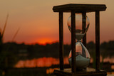 hourglass counts down the time on the sunset pond
