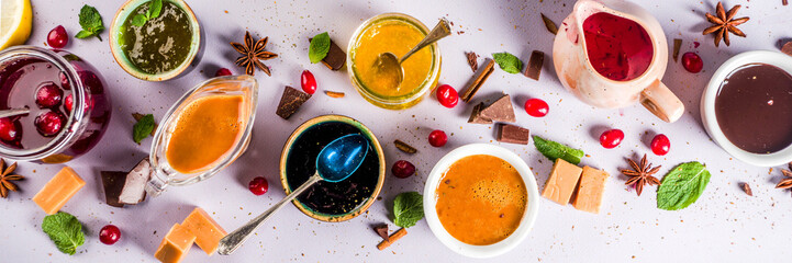 Various sweet sauces, toppings and syrups - lemon, orange, caramel, chocolate, cranberry, cherry, blueberry, on a light concrete background, top view copy space for text banner © ricka_kinamoto