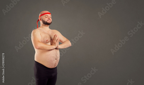 Wall mural A bearded man with a naked stomach doing yoga on a gray background for text.