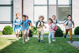 group of adorable pupils runing by school garden