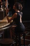 elegant lady in black dress, in restaurant at a bar - 218025290