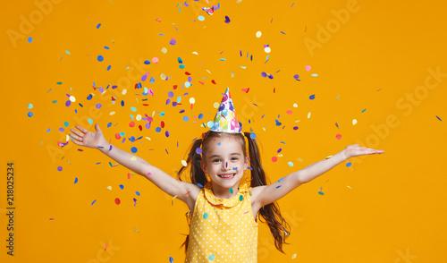 Leinwanddruck Bild happy birthday child girl with confetti on yellow background