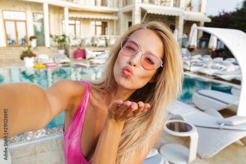 Leinwanddruck Bild Happy young woman in swimsuit, sunglasses
